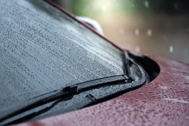 Samochody zaparkowane w deszczu w porze deszczowej i wyposażone w system wycieraczek do czyszczenia przedniej szyby z przedniej szyby