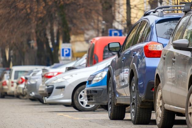 Samochody zaparkowane w rzędzie od strony ulicy miasta.