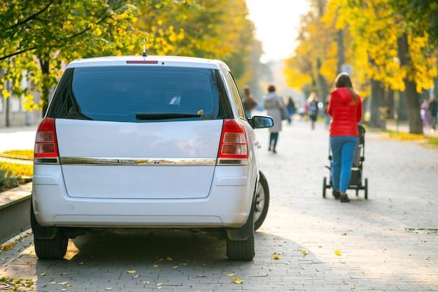Samochody zaparkowane w rzędzie po stronie ulicy miasta w jasny jesienny dzień z niewyraźnymi ludźmi chodzącymi na deptaku.