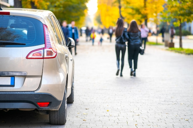 Samochody zaparkowane z rzędu na stronie ulicy miasta w jasny jesienny dzień z niewyraźnymi ludźmi chodzącymi po deptaku.