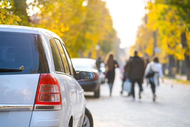 Samochody zaparkowane z rzędu na stronie ulicy miasta w jasny jesienny dzień.