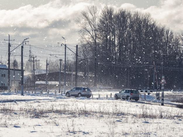 Samochody zimą przejeżdżają przez przejazd kolejowy poza miastem. przejazd kolejowy. zimowy krajobraz ze śniegiem pokryte drzewami i słońcem.
