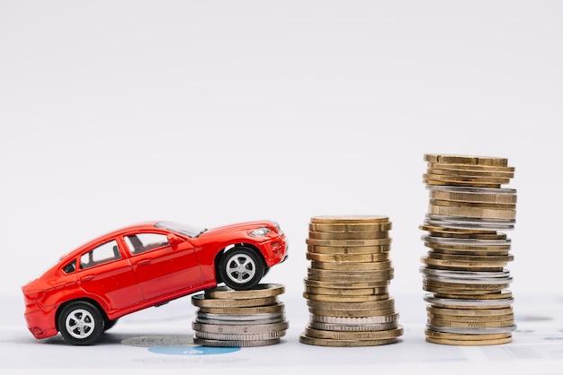 Samochodzik idzie się na rosnącej stos monet na białym tle