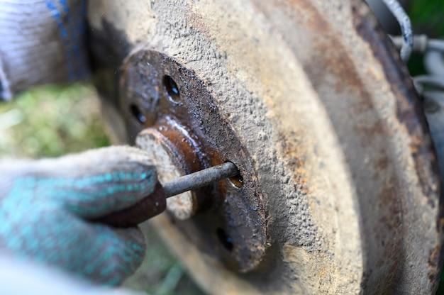 Samodzielna naprawa hamulca bębnowego w męskich rękawiczkach. demontuje zablokowany dysk za pomocą śrubokręta. naprawa uszkodzonego hamulca bębnowego samochodu zdemontowanego na zewnątrz