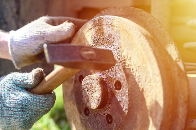 Samodzielna naprawa hamulca bębnowego w męskich rękawiczkach. demontuje zakleszczony dysk młotkiem. naprawa uszkodzonego hamulca bębnowego samochodu zdemontowanego na zewnątrz. migotać