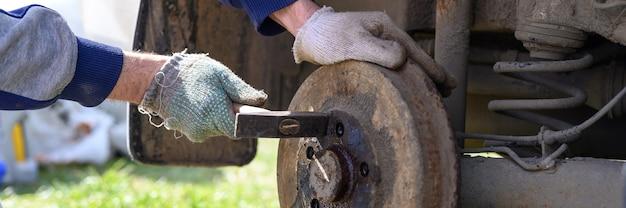 Samodzielna naprawa hamulca bębnowego w męskich rękawiczkach. demontuje zakleszczony dysk młotkiem. naprawa uszkodzonego hamulca bębnowego samochodu zdemontowanego na zewnątrz. transparent