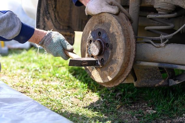 Samodzielna naprawa hamulca bębnowego w męskich rękawiczkach. demontuje zakleszczony dysk młotkiem. naprawa uszkodzonego hamulca bębnowego samochodu zdemontowanego na zewnątrz