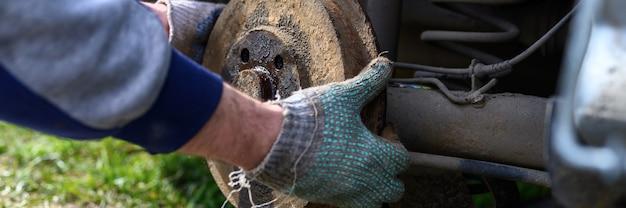 Samodzielna naprawa hamulca bębnowego w męskich rękawiczkach. naprawa uszkodzonego hamulca bębnowego samochodu zdemontowanego na zewnątrz. transparent