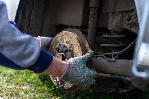Samodzielna naprawa hamulca bębnowego w męskich rękawiczkach. naprawa uszkodzonego hamulca bębnowego samochodu zdemontowanego na zewnątrz