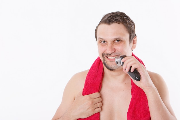 Samodzielnie na białej ścianie: mężczyzna goli zarost. facet czyści brodę elektryczną maszynką do golenia. poranne zabiegi w łazience. czerwony ręcznik na szyi. skopiuj miejsce