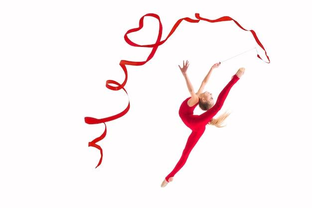 Samodzielnie na białym tle gimnastyczka dziewczyna skoków z czerwoną wstążką skręcania serc.