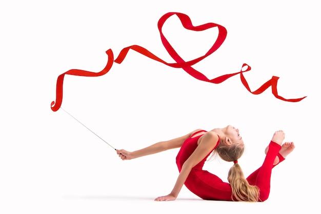 Samodzielnie na białym tle gimnastyczka dziewczyna w czerwonym kombinezonie wykonuje ćwiczenia ze wstążką, wstążka jest skręcona w serce.