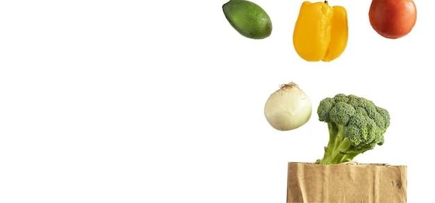 Samodzielnie na białym tle lewitujący warzywa pomidor, papryka, awokado, cebula, brokuły nad papierową torbę na zakupy. koncepcja usługi dostawy.