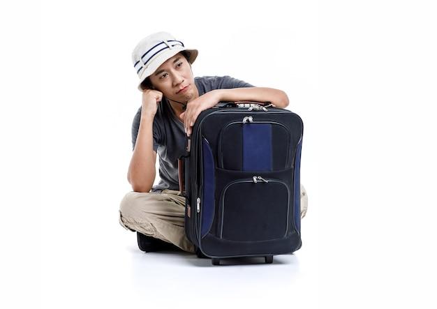 Samodzielnie studyjny strzał azjatyckich niezadowolony znudzony mężczyzna przygoda podróżnik nosić wiadro kapelusz siedzący na podłodze przytulić przytrzymaj wózek podróżny bagaż czeka na opóźnienie transportu na wakacjach na białym tle.