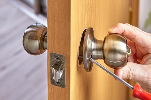 Samodzielny montaż mechanizmu zamka drzwi z uchwytami w nowym drewnianym panelu.