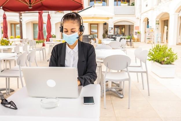 Samodzielny przedsiębiorca pracujący przy stoliku barowym na świeżym powietrzu przy użyciu laptopa noszącego ochronną medyczną maskę na twarz
