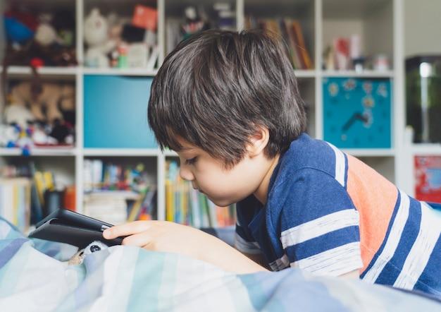 Samoizolacja dziecka za pomocą tabletu w odrabianiu lekcji, dziecko w łóżku za pomocą cyfrowego tabletu, wyszukiwanie informacji w internecie, edukacja domowa, dystans społeczny, e-learning edukacja online