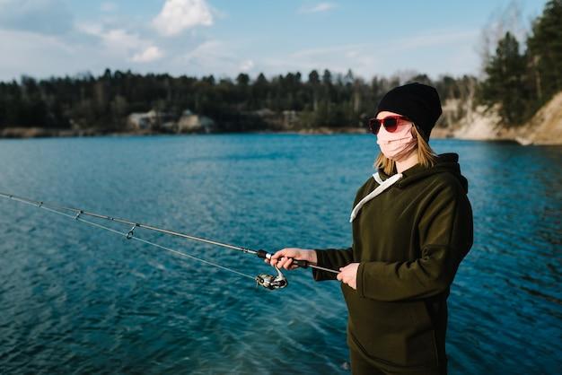 Samoizolacja w przyrodzie, ochrona, koronawirus. rybaczka, pręt, kołowrotek na brzegu jeziora.