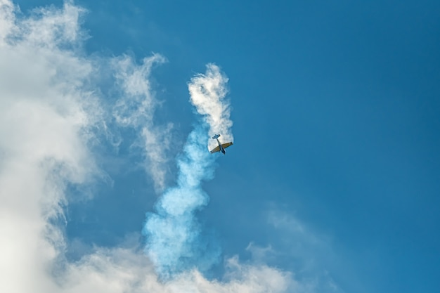 Samolot akrobacyjny ze śladem dymu na niebie