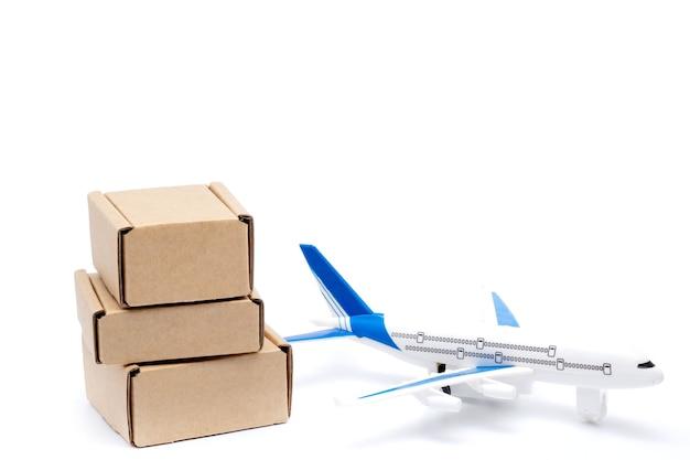 Samolot cień i stos kartonów na białym tle. koncepcja ładunku lotniczego i paczek, poczta lotnicza. szybka dostawa towarów i produktów. logistyka, połączenie z trudno dostępnymi miejscami