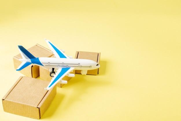 Samolot i stos kartonów. koncepcja ładunku lotniczego i paczek, poczta lotnicza. szybka dostawa towarów i produktów.