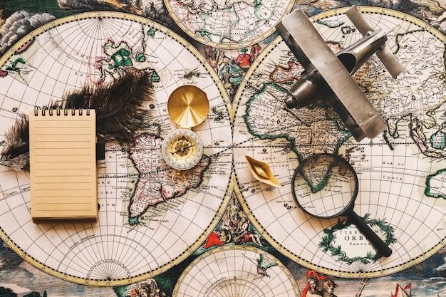 Samolot i szkło powiększające w pobliżu kompasu i notebooka