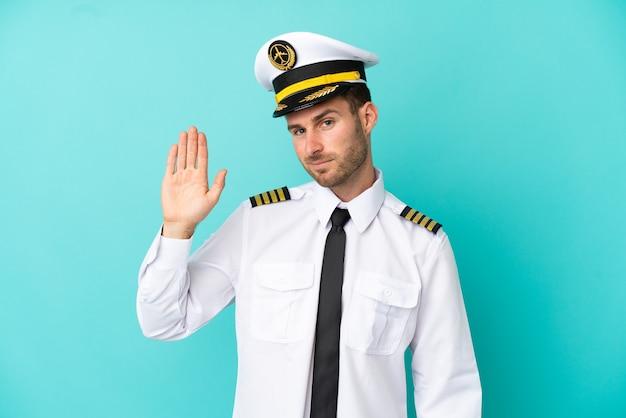 Samolot kaukaski pilot na białym tle na niebieskim tle pozdrawiając ręką ze szczęśliwym wyrazem twarzy