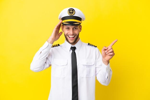 Samolot kaukaski pilot na białym tle na żółtym tle zaskoczony i wskazujący palcem w bok