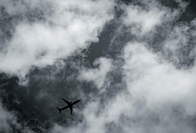 Samolot latający na ciemne niebo i białe chmury. komercyjne linie lotnicze z koncepcją wymarzonych miejsc docelowych. koncepcja kryzysu biznesu lotniczego. nieudany lot na wakacje. transport powietrzny.