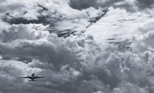 Samolot latający na ciemne niebo i białe puszyste chmury.