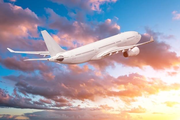 Samolot latający nabierający wysokości wieczorem o zachodzie słońca, na niebie i malowniczych chmurach.