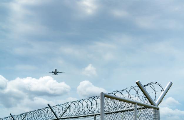 Samolot lecący na błękitne niebo i białe chmury nad metalowym ogrodzeniem