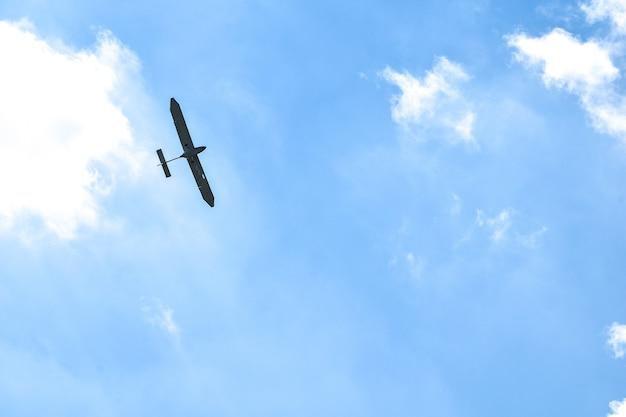 Samolot lecący w błękitne niebo na tle białych chmur, widok z tyłu