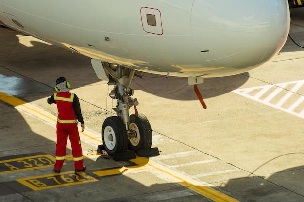 Samolot na lotnisku obsługiwany przez obsługę naziemną przed odlotem na lotnisku donmueang