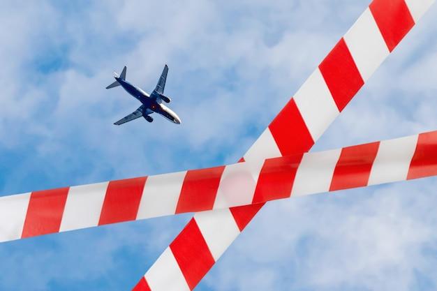 Samolot na niebie, zakaz podróży lotniczych, taśma odgradzająca, kwarantanna, izolacja, nie przekraczaj