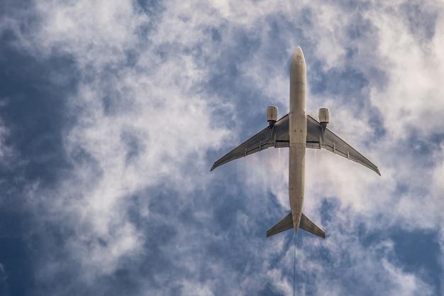 Samolot na niebieskim niebie z chmurami. podróżuj po świecie w powietrzu