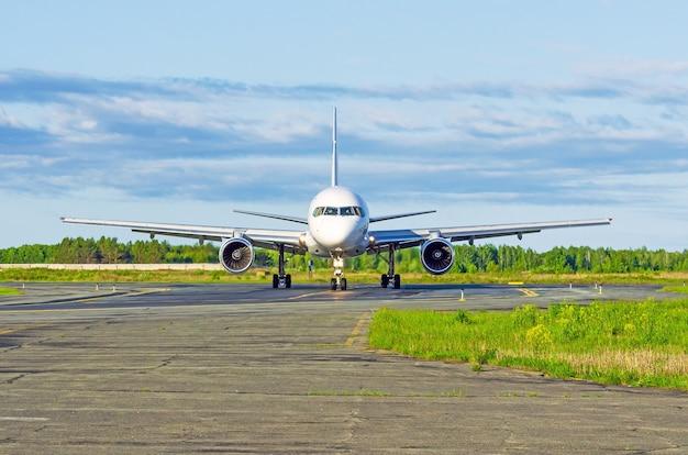 Samolot na pasie startowym to widok z przodu silnika i podwozia