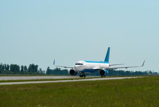 Samolot pasażerski jeździ po pasie startowym lotniska.