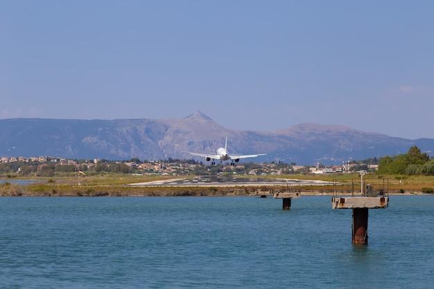 Samolot pasażerski ląduje na lotnisku w kerkyra. grecja, wyspa korfu. zmniejszenie wysokości. pas startowy na tle gór i morza.