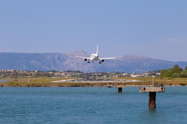 Samolot pasażerski ląduje na lotnisku w kerkyra. grecja, wyspa korfu. zmniejszenie wysokości, zbliżenie. pas startowy na tle gór i morza.