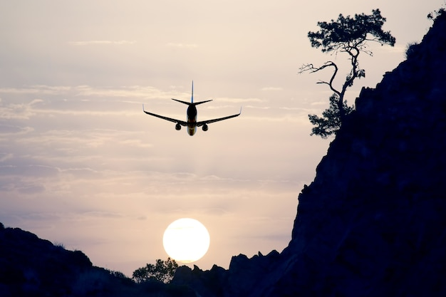 Samolot pasażerski lecący na wieczornym niebie o zachodzie słońca