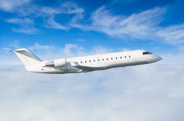 Samolot pasażerski leci na poziomie lotu na tle chmur i błękitnego nieba