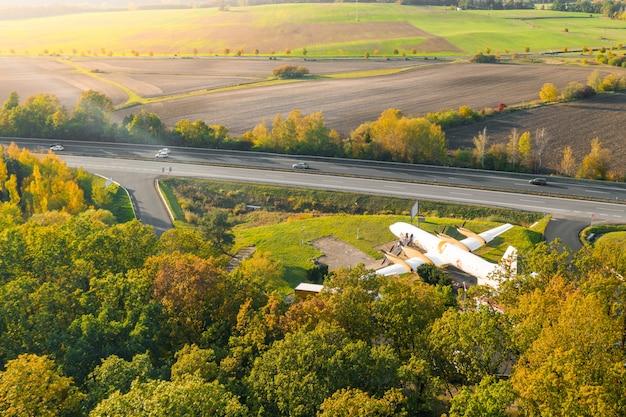 Samolot pasażerski na polu w pobliżu lasu. płaska restauracja przy autostradzie otoczona drzewami liściastymi. mlada boleslav,