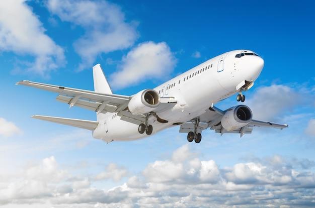 Samolot pasażerski z podwoziem wydanym przed lądowaniem na lotnisku na tle błękitnego nieba.