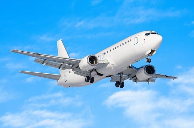 Samolot pasażerski z podwoziem zwolnionym przed lądowaniem na lotnisku na tle błękitnego nieba.