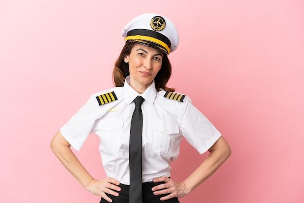 Samolot pilot w średnim wieku kobieta na białym tle na różowym tle pozuje z rękami na biodrach i uśmiecha się