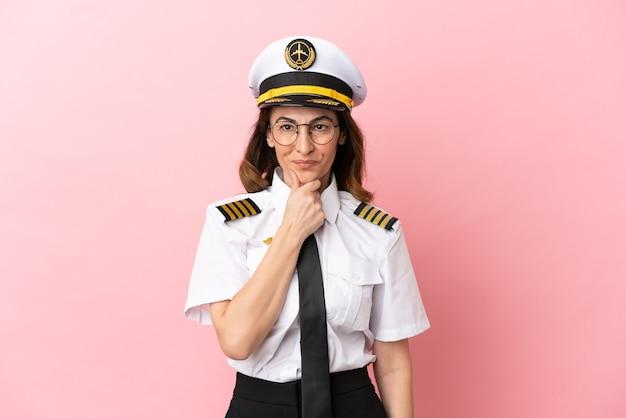 Samolot pilot w średnim wieku kobieta na białym tle na różowym tle w okularach i uśmiechnięty
