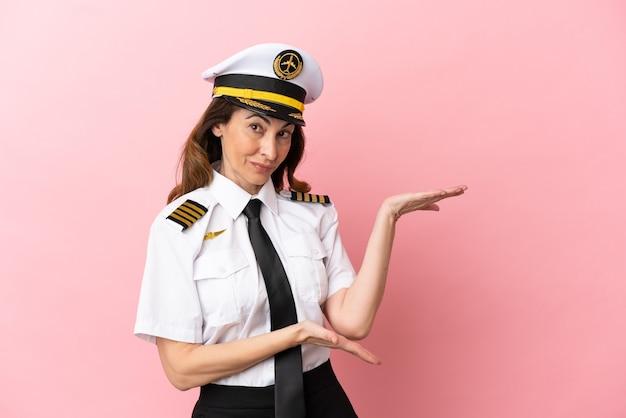 Samolot pilot w średnim wieku kobieta na białym tle na różowym tle wyciągając ręce do boku za zaproszenie do przyjścia