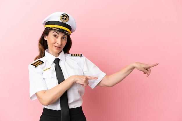 Samolot pilot w średnim wieku kobieta na białym tle na różowym tle zaskoczony i wskazujący bok