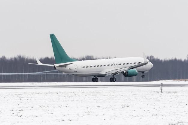Samolot startuje z pokrytego śniegiem lotniska pasa startowego przy złej pogodzie podczas burzy śnieżnej, silnego wiatru zimą.